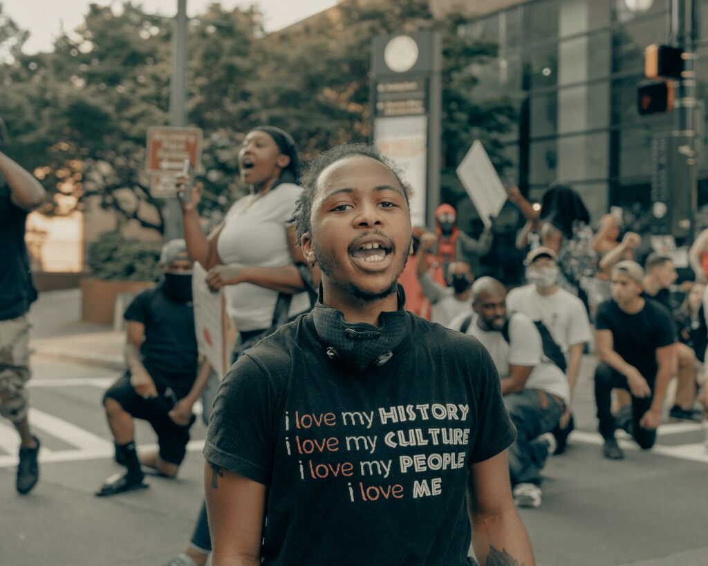 """Black activist at a protest, wearing a t shirt that says """"i love my history, i love my culture, i love my people, i love me"""""""