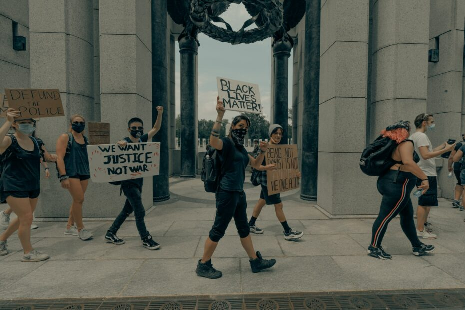 """White allies marching in a protest with signs that say """"Black Lives Matter"""" and """"Defund the Police"""""""