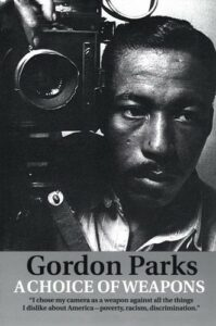 """Gordon Parks with camera, text reads """"A Choice of Weapons"""" with quote """"I chose my camera as a weapon against all the things I dislike about America -- poverty, racism, discrimination."""""""